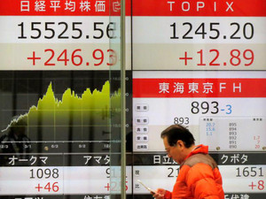 A pedestrian walks in front of a quotation board displaying the Nikkei key index of the Tokyo Stock Exchange (L) and TOPIX (R) in Tokyo on December 18, 2013