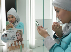 An Indonesian woman applies lipstick at a Wardah outlet, Indonesia's Islamic brand cosmetic in Jakarta on May 8, 2013