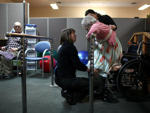 A physical therapist helps a patient stand up during a physical therapy session on February 10, 2011 in Novato, California