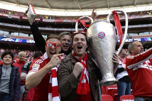 Bayern Munich supporters holding a model of the trophy in the crowd at Wembley Stadium in London on May 25, 2013