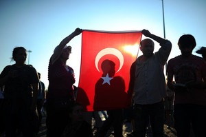 People hold a Turkish national flag as they stand on the flashpoint Taksim square in Istanbul on June 18, 2013