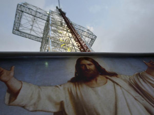 A Christian man hangs a banner depicting of Jesus Christ in front of a towering cross in the village of Qanat Bekish, in the Lebanese mountains on September 13, 2010