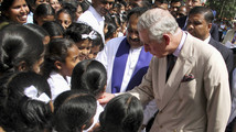 Britain's Prince Charles talks with children during visit to temple, in Kandy