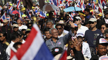 Anti-government protest leader Suthep Thaugsuban gestures to his supporters as he marches during a rally at a major business district in Bangkok