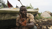 A fisherman shows oil slick on his palm, by the shore of the Niger Delta region in Brass