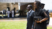 Zimbabwe's President Mugabe and his wife Grace hold hands after paying their respects at coffin of former South African President Nelson Mandela as he lies in state at Union Buildings in Pretoria
