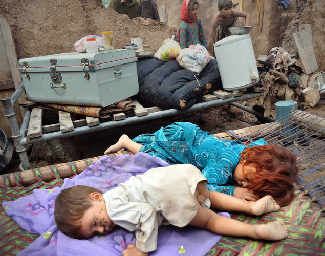 Pakistani children sleep on a charpoy (rope bed) as others (background) work in the compound of their collapsed house following floods.