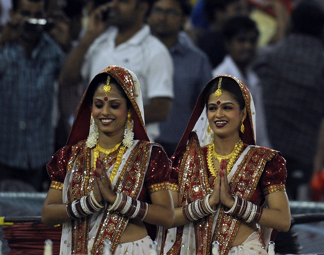 Pune Warriors cheerleaders in traditional costume gesture as they arrive prior to the IPL Twenty20 cricket match between Kings XI Punjab and Pune Warriors at PCA Stadium.