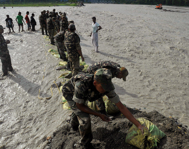 Indian army personal repair a dam damaged by flood waters at Milanmore village on the outskirts of Siliguri.