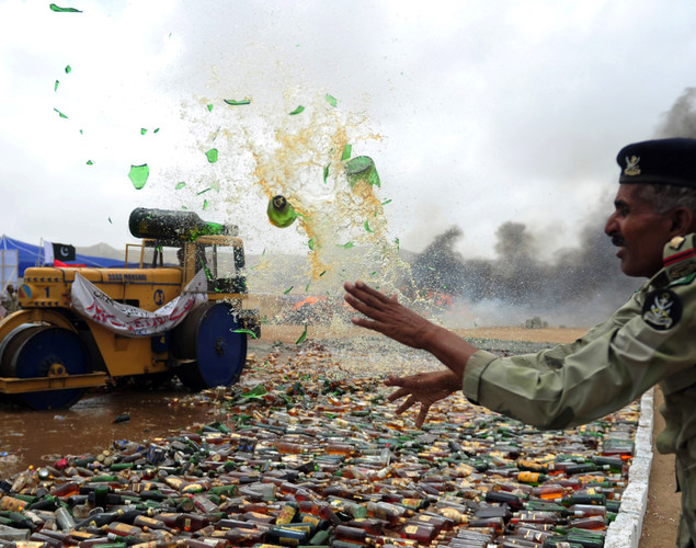 A Pakistani soldier destroys seized bottles of liquor during a ceremony to mark International Day against Drug Abuse and Illicit Trafficking, in Karachi.