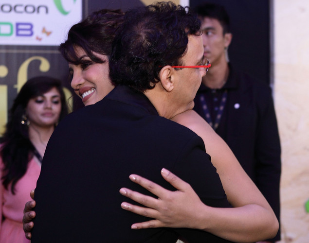 Bollywood actress Priyanka Chopra (R) shares a hug with Rajesh Maspukar at the IIFA green carpet event at the 2012 International India Film Academy Awards at the Singapore Indoor Stadium.