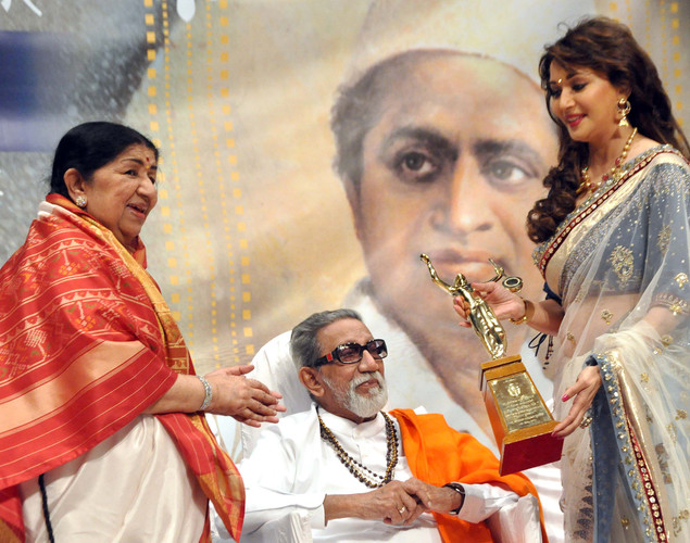 Legendary playback singer Lata Mangeshkar, (L), politician Shiv Sena chief Bal Thackeray (C) and film actress Madhuri Dixit Nene attend the 'Deenanath Mangeshkar Puraskar Awards 2012' ceremony in Mumbai.
