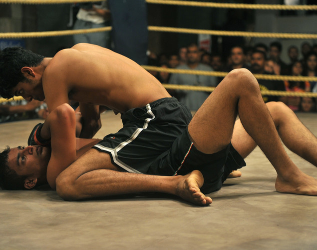 Mixed Martial Arts (MMA) fighters Sumeet Sawant (on ground) is pinned by opponent Sumeet Khade in their bout during the FCC (Full Contact Championship) 6 fight night in Mumbai.