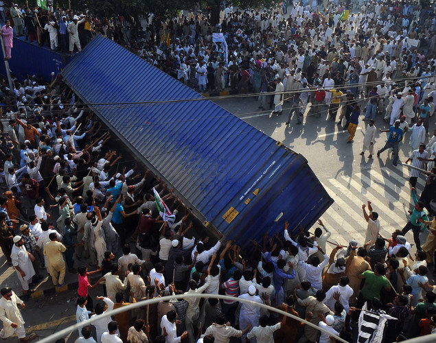 Pakistani Muslim demonstrators topple a freight container, placed by police to block a street during a protest against an anti-Islam film in Lahore.