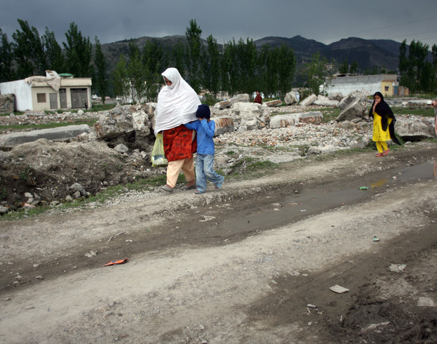 Local residents walk past the rubble of the demolished compound of slain Al-Qaeda leader Osama bin Laden in northern Abbottabad.