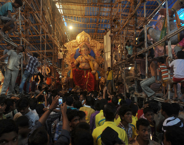 Onlookers climb onto scaffolding to catch a glimpse of a huge idol of the elephant-headed Hindu god Lord Ganesha as it is readied in a workshop to be carried by Indian Hindus through the busy streets of Mumbai.