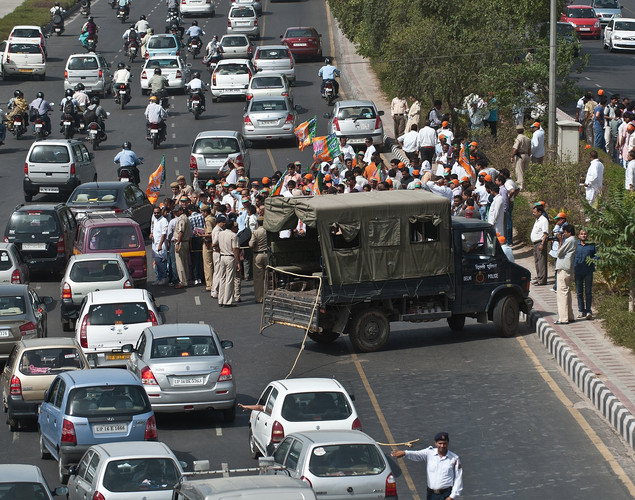 Traffic passes by as police cordon off demonstrating Bharatiya Janata party (BJP) activists blocking a road during a protest against a petrol price hike in New Delhi.