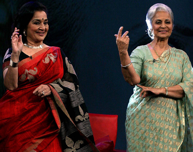 "Waheeda Rehman (R) and Asha Parekh perform onstage during the NDTV talk show ""Issi Ka Naam Zindagi"" in Mumbai on April 19, 2012."