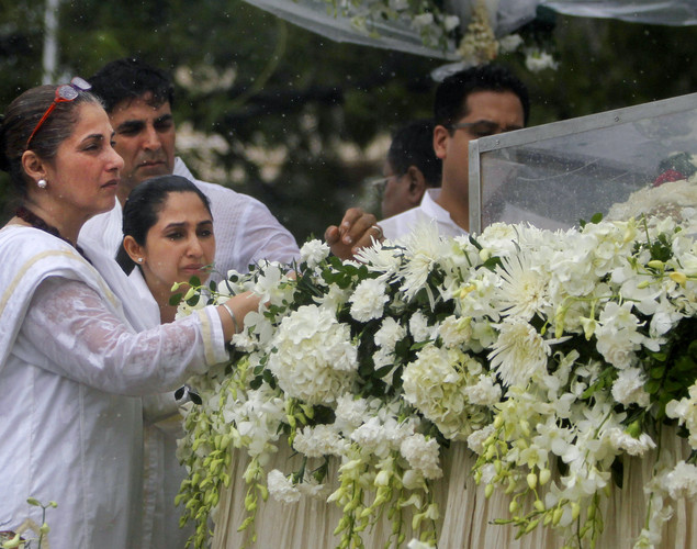 Actress Dimple Kapadia, the wife of late Bollywood superstar Rajesh Khanna, left, along with her daughter Rinke Khanna, second from left and son-in-law, actor Akshay Kumar, background left, pay their respects during Khanna's funeral in Mumbai.