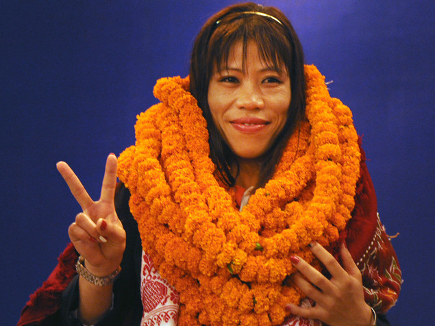 In this photograph taken on August 14, 2012, Indian women's boxing champion and Olympic Bronze medal winner Mary Kom, wearing marigold garlands presented by well-wishers, gestures during a reception in New Delhi.