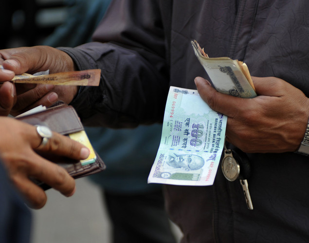 A man holds Indian rupee notes in New Delhi.