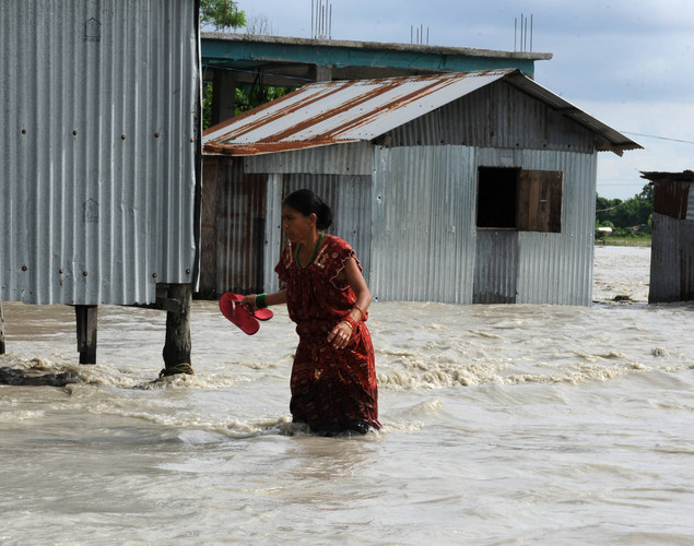 Indian residents wade through flood waters at Milanmore village on the outskirts of Siliguri.