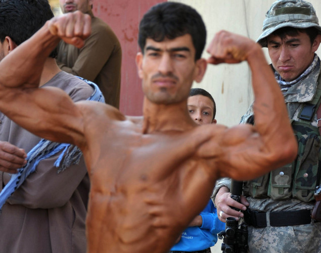 An Afghan policmen looks at an Afghan bodybuilder getting ready to preform in the Mr. Afghanistan nation wide bodybuilding competition in Kabul. Bodybuilding is one of the country's most popular sports, even permitted during the 1996-2001 Taliban regime.