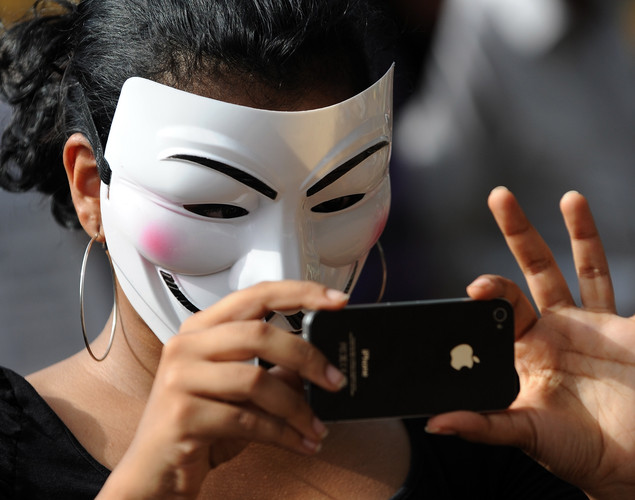 An activist supporting the group Anonymous wears a mask as she takes a picture during a protest against the Indian Government's increasingly restrictive regulation of the internet in Mumbai.