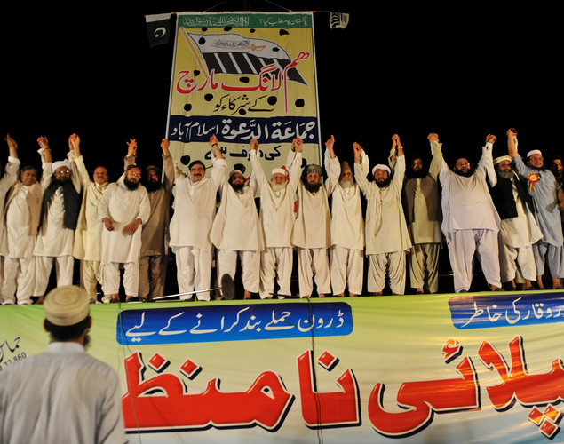 Leaders of the Defense of Pakistan coalition raise their hands in a show of solidarity during a protest rally in Islamabad.