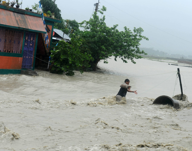 Indian villagers wade through flood waters in the Milanmore village on the outskirts of Siliguri.