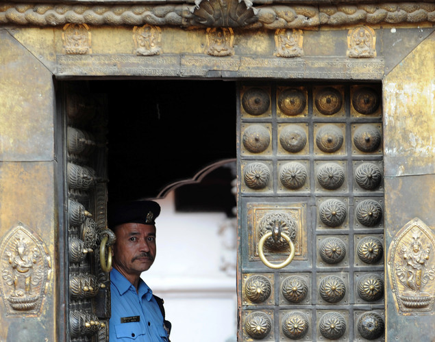 A Nepalese policeman stands guard at Durbar Square in Lalitpur on August 23, 2011. Lalitpur's Durbar Square, a UNESCO World Heritage Site, is best known for its rich cultural heritage, particularly its tradition of arts and crafts.