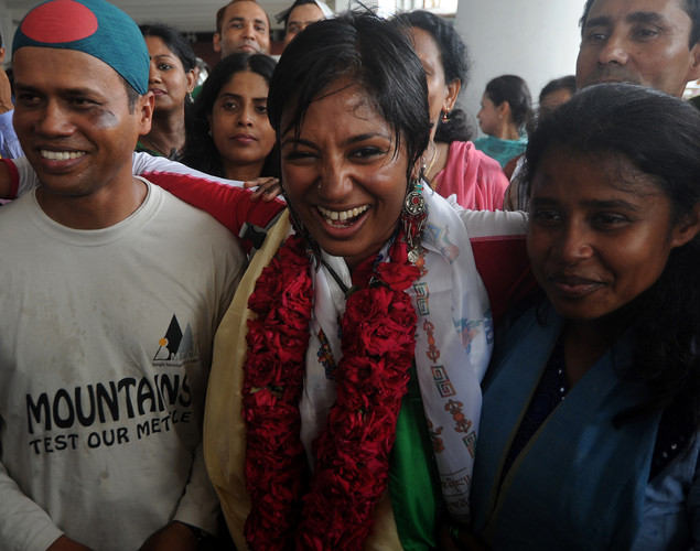 Bangladeshi mountaineer Wasfia Nazreen (C) , M.A. Muhit (L), and climber Nishat Majumder (R) pose for a photo with fans after arriving at the Hazrat Shahjalal International Airport in Dhaka.