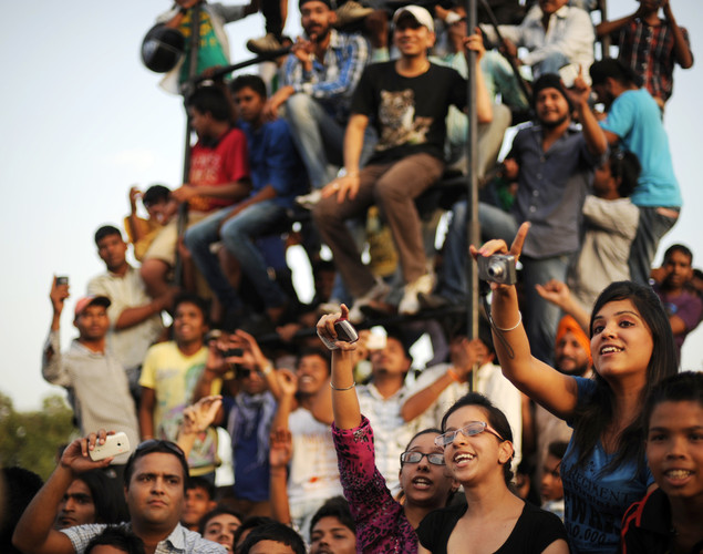A crowd of people cheer during a motorcycle street show near India Gate in New Delhi.