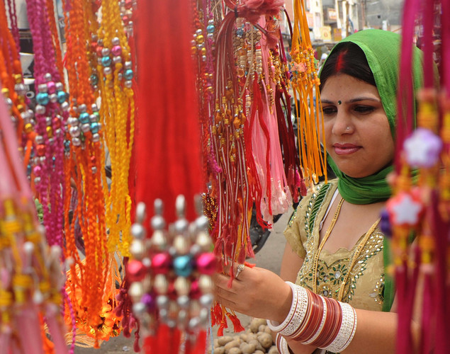 An Indian consumer looks at 'rakhi' (sacred thread) on the eve of the Hindu festival Raksha Bandhan in Amritsar.