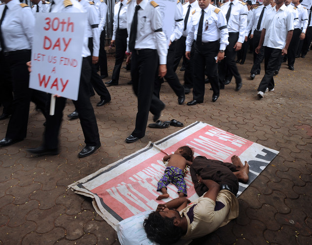 A homeless father and child take a nap as members of the Indian Pilots' Guild participate in a silent protest march on the 30th day of their strike in Mumbai.