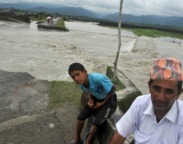 Indian residents sits near a road washed out by flood waters at Milanmore village on the outskirts of Siliguri.