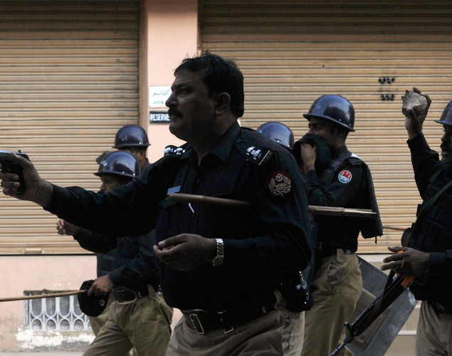 A Pakistani police officer (front) fires his sidearm towards demonstrators during a protest against an anti-Islam film in Lahore.
