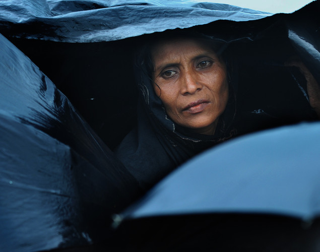 A Rohingya Muslim woman, fleeing sectarian violence in Myanmar, is pictured taking shelter under a tarp while on an intercepted boat trying to cross the Naf river into Bangladesh in Teknaf.