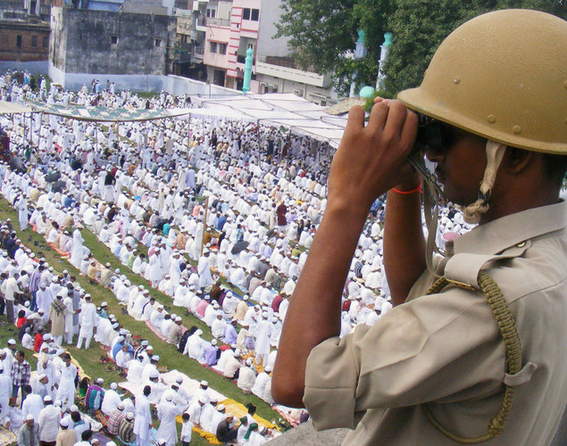 A policeman watches Indian Muslims offering Eid al-Fitr prayers in Allahabad.