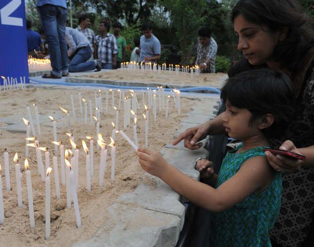 A young Indian participant lights a candle at the Blind People's Association in Ahmedabad on the eve of Hindu festival Raksha Bandhan.