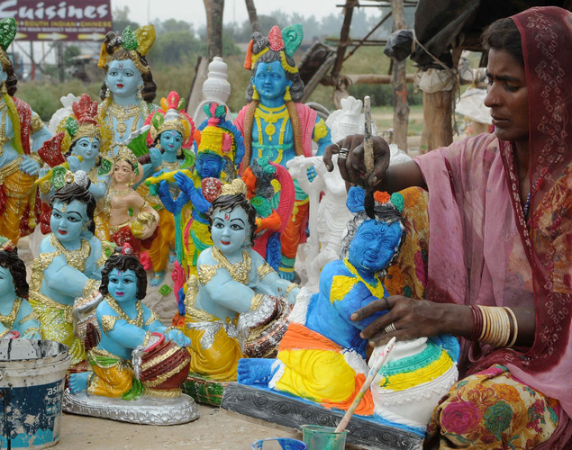 An Indian artist Rukee paints an idol of Hindu Lord Krishna at a roadside stall on the outskirts of Amritsar on August 8, 2012.