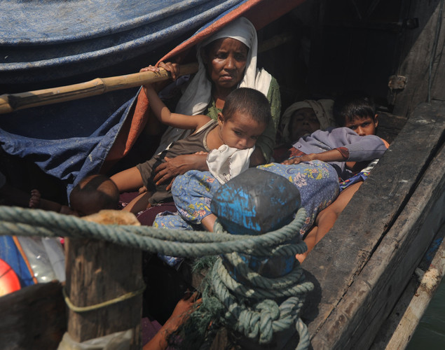 Rohingya Muslims fleeing sectarian violence are seen on a boat as they try to cross the Naf river into Bangladesh in Teknaf.