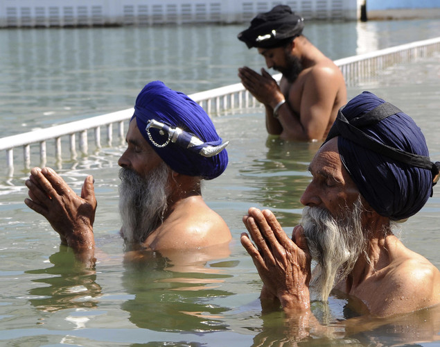 Indian Sikh devotees pay their respects as they take a holy dip in the sarover (water tank) at the Sikh Shrine Golden Temple in Amritsar.