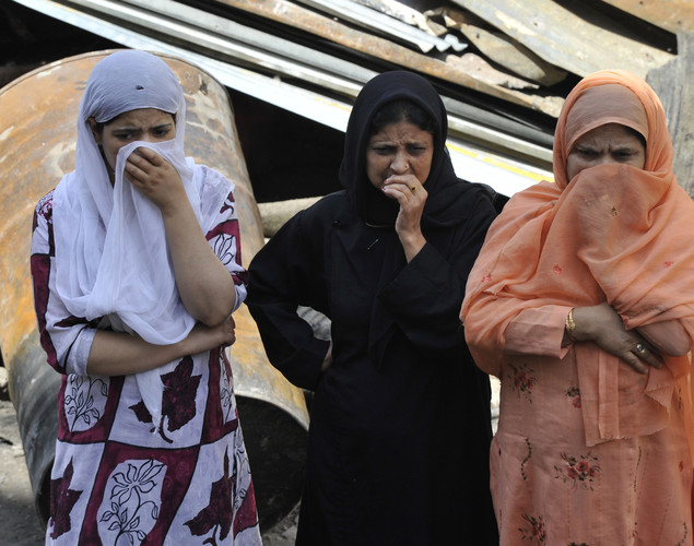 Kashmiri women grieve as they look on at the charred remains of the 200-year old shrine of Sheikh Abdul Qadir Jeelani, also known as Dastigheer Sahib, in downtown Srinagar.