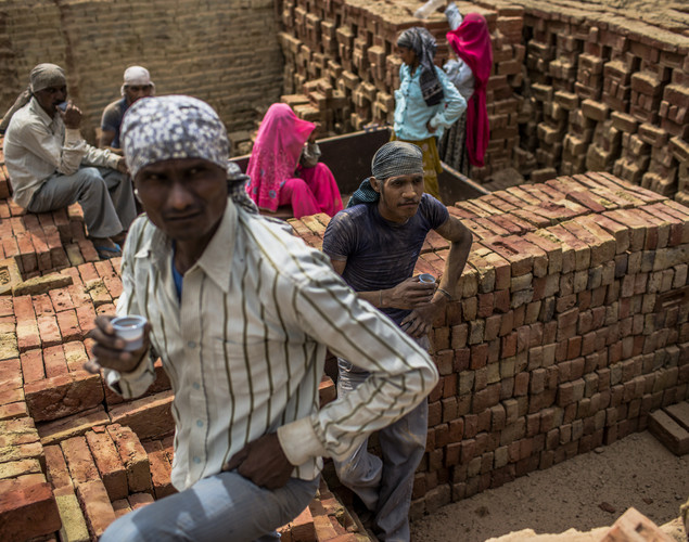 Laborers drink tea during a break from loading baked bricks onto a truck at a brick making facility on May 23, 2012 in a village near Jaipur, India.