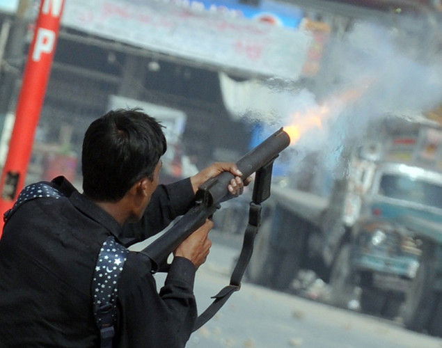 A Pakistani policeman fires tear gas shell toward the protesters belonging Islami Jamiat-e-Talaba, a student wing of the hard line Sunni party Jamaat-e-Islami (JI), near the US consulate during a protest against an anti-Islam movie in Karachi.