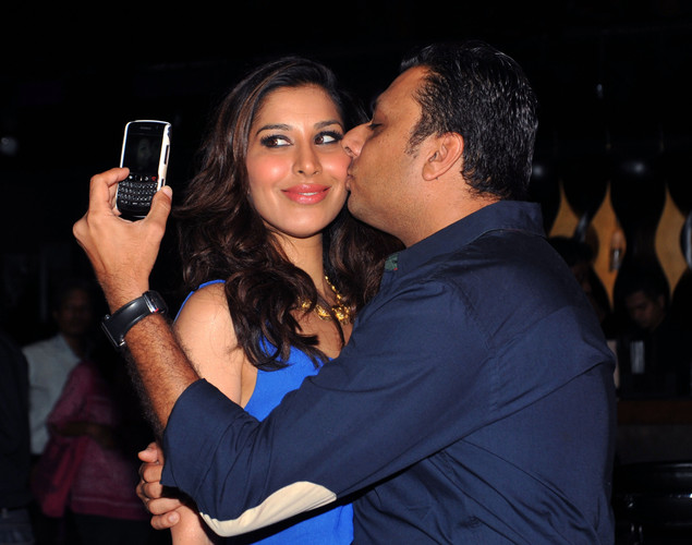 Indian actress and Sophie Choudhry (L) poses for a photograph with a guest during the DJ Mag launch event in Mumbai.