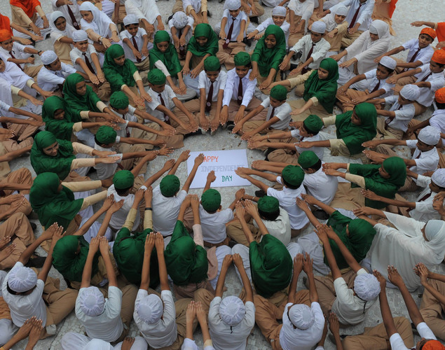 Anjuman-E-Islam schoolchildren, wearing colours of the Indian national flag, pose as they make a pledge on the eve of Independence Day in Ahmedabad on August 14, 2012.