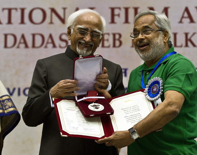 Indian Vice President Hamid Ansari (L) presents the best film on social issues award to Director Arun Chadha during the 59th National Film Award in New Delhi.