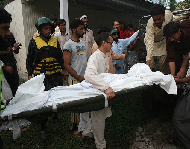 Pakistani men carry into a jeep, the dead body of a victim who was swept away in the flood waters.